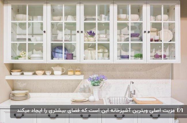 آشپزخانه با کابینت های یک طرفه سفید رنگ و تبدیل کابینت های بالایی به ویترین هایی با درب شیشه ای