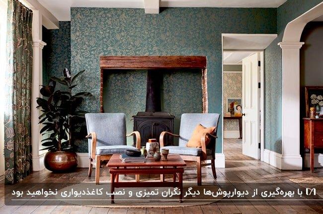 دکوراسیون داخلی اتاق پذیرایی با دیوارپوش طرحدار سبز، شومینه و دو صندلی چوبی آبی