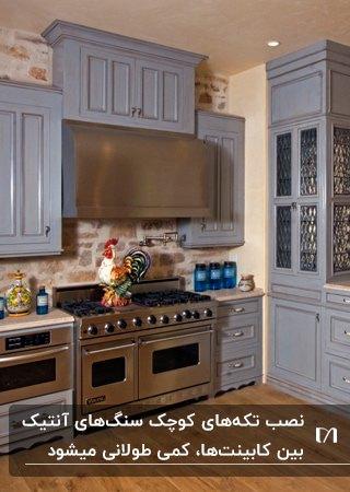 آشپزخانه ای سنتی با کابینت های آبی روشن، گازو هود نقره ای و دیوارپوش های بین کابینتی سنگ آنتیک