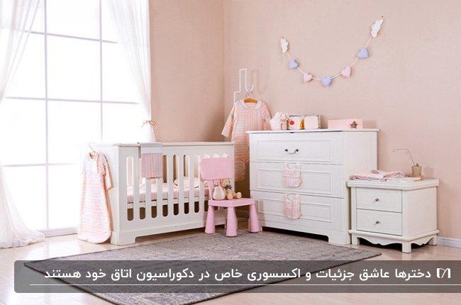 دکوراسیون اتاق دخترانه کودک با دیوارهای صورتی، تخت، دراور و پاتختی سفید کنار پنجره