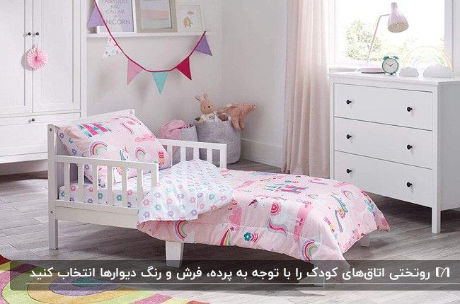 تصویر دکوراسیون یک اتاق دخترانه با سرویس خواب سفید و رو تختی صورتی با طرح های کارتونی