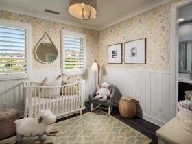 تصویر دکوراسیون یک اتاق کودک با سرویس خواب سفید، صندلی راک کودکانه طرح گوسفند، آینه و تایبوی دیواری و کاغذدیواری طرحدار زرد کمرنگ