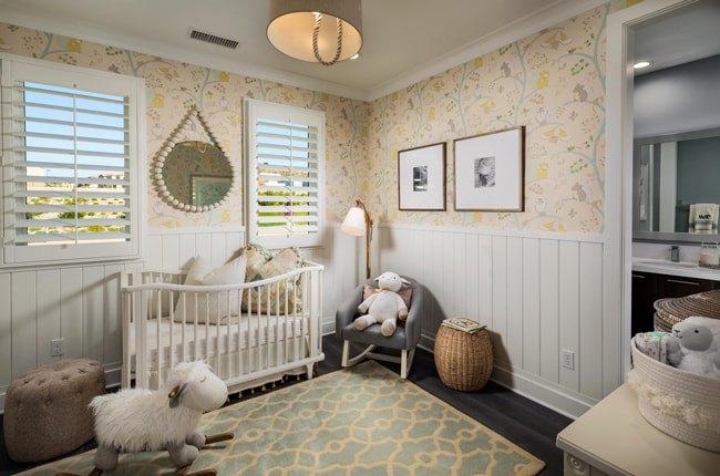 تصویر دکوراسیون یک اتاق کودک با سرویس خواب سفید، صندلی راک کودکانه طرح گوسفند