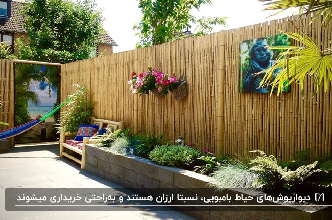 حیاطی با دیوارپوش بامبویی، باغچه کنار دیوار و صندلی ننویی بدون پایه آویز