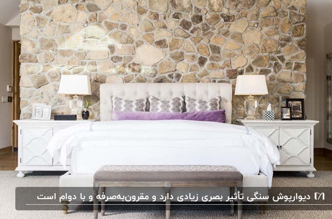 دکوراسیون اتاق خوابی با دیوارپوش سنگی، کوسن های بنفش و دو پاتختی و آباژور