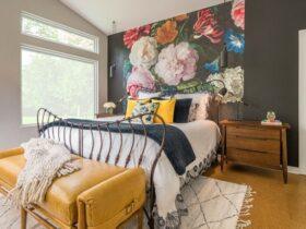 دکوراسیون اتاق خوابی با دیوارپوش گلدار، تخت و پاتختی چوبی و پاف خردلی