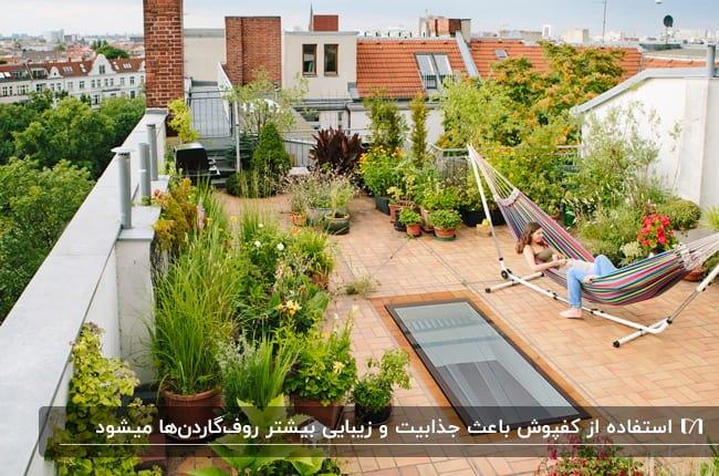 روفگاردنی با گل ها و گیاهان طبیعی فراوان، تاب آویز و کفپوش قهوه ای روشن