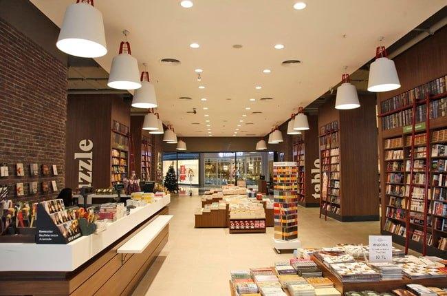 تصویر یک کتاب فروشی با قفسه های چوبی قهوه ای، چراغ های آویز و هالوژن ها و میز رسپشن قهوه ای
