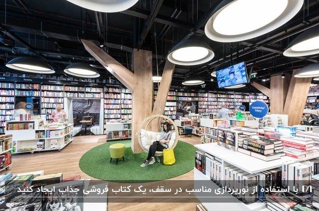 کتاب فروشی بزرگی با قفسه های سفید رنگ و سقف مشکی با چراغ های آویز نیم دایره ای