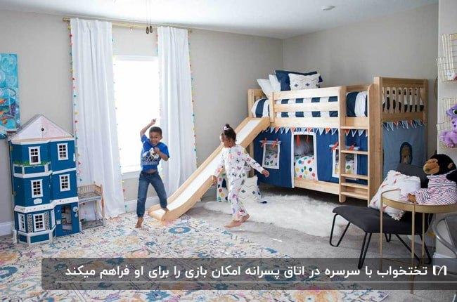 دکوراسیون اتاق پسرانه با تخت دو طبقه چوبی و آبی تیره به همراه سرسره