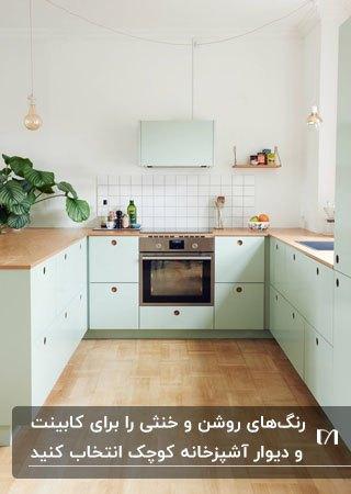 آشپزخانه ای کوچک و کم جا با کابینت های سبز روشن و صفحه رویی چوبی