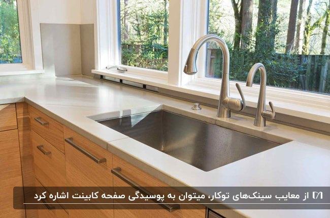 تصویر آشپزخانه ای با کابینت قهوه ای و صفحه رویی کابینت سفید به همراه سینک توکار نقره ای