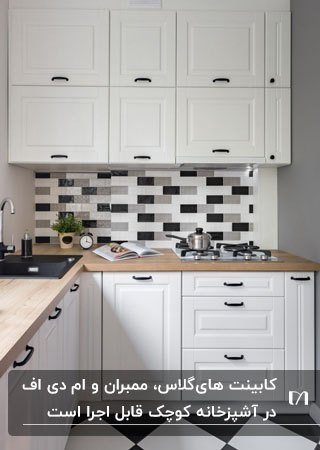 کابینت های سفید چوبی با کاشی های بین کابینتی سفید و مشکی و صفحه رویی چوبی