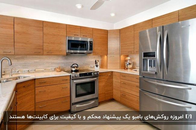 آشپزخانه ای با لوازم برقی سیلور و کابینت هایی با روکش بامبو قهوه ای