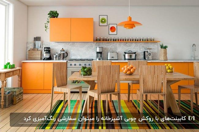 آشپزخانه ای با روکش های کابینت نارنجی،فرش راه راه رنگی و میز و صندلی های غذاخوری چوبی