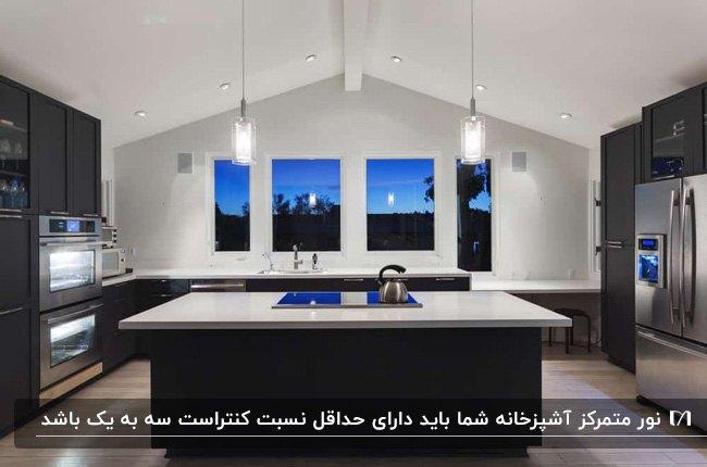 آشپزخانه ای با سقف شیبدار، کابینت ها و جزیره زغالی، صفحه رویی سفید کابینت و نورپردازی متمرکز آویز