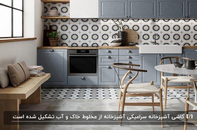 آشپزخانه ای با کابینت های طوسی، میز و صندلی های غذاخوری چوبی و کاشی های بین کابینتی سفید طرحدار