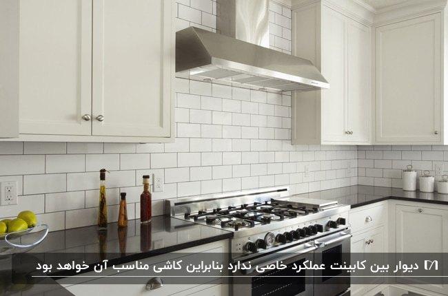 آشپزخانه ای با کابینت های سفید و کاشی های بین کابینتی سفید با گاز و هود نقره ای