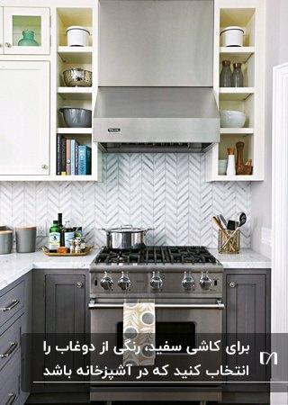 آشپزخانه ای با کابینت های خاکستری، صفحه رویی کابینت سفید و کاشی بین کابینتی سفید با دوغاب طوسی