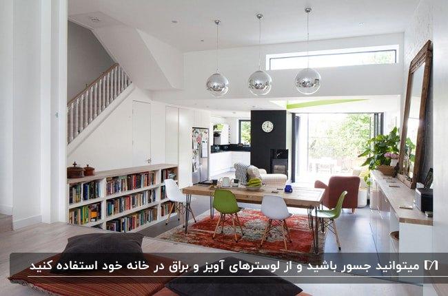 خانه ای دوبلکس با کفپوش چوبی، کتابخانه دیواری، فرش قرمز، میز و صندلی های غذاخوری سبز و سفید و لوسترهای دایره ای نقره ای