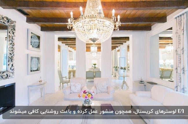 نشیمنی با دیوارها و مبلمان سفید، سقف با تیرهای چوبی قهوه ای و لوستر آویز کریستالی