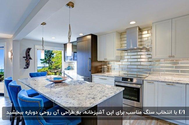 آشپزخانه ای با کابینت های سفید و قهوه ای، صندلی های پایه دار آبی و سنگ سفید اپن با رگه های طوسی