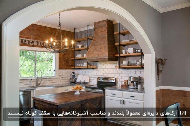 آشپزخانه ای با کابینت های سفید و قفسه های دیواری چوبی و آرک دایره ای گچی سفید