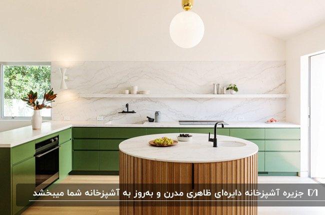 آشپزخانه بزرگی با کابینت های مدرن سبز رنگ و جزیره دایره ای چوبی