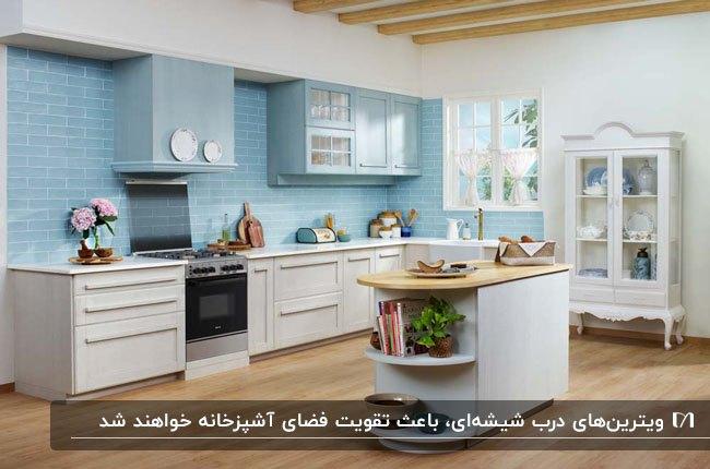 آشپزخانه ای با کابینت های سفید و دیوار بین کابینت آبی به همراه ویترین با درب چوبی و شیشه ای