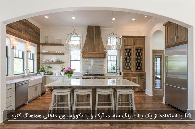آشپزخانه بزرگی با کابینت ها و جزیره چوبی سفید و قهوه ای و آرک گرد گچی