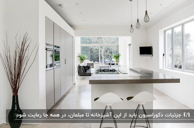آشپزخانه ای با کابینت ها و کانتر سفید و صفحه رویی چوبی با دو صندلی سفید و یک گلدان گل مشکی