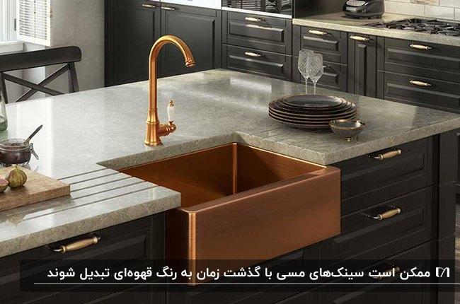آشپزخانه ای با کابینت های مشکی، صفحه رویی کابینت سفید و سینک و شیر آب مسی