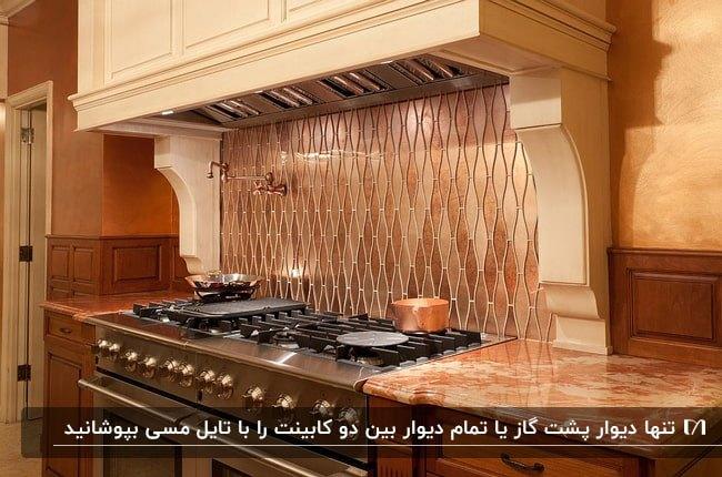 آشپزخانه ای با تم رنگی کرم و قهوه ای و دیوارپوش پشت اجاق گاز فلزی به رنگ مسی