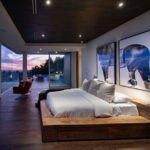 اتاق خواب لاکچری ای با یک دیوار شیشه ای، تخت دو نفره چوبی و دو تابلوی نقاشی بزرگ بالای تخت