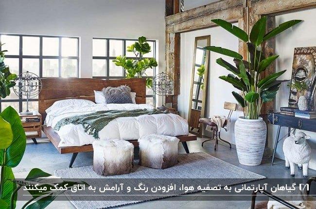 اتاق خوابی با تخت دو نفره قهوه ای، آینه مستطیلی بلند، دو پاف دایره ای و گلدان های گل آپارتمانی