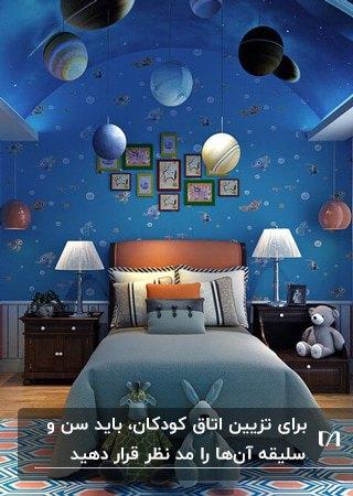 اتاق خواب پسرانه ای با کاغذدیواری، لوستر و تم کهکشانی به رنگ آبی و نارنجی