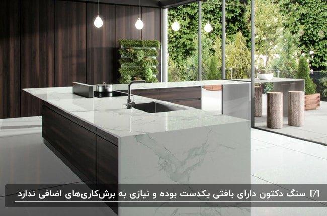 آشپزخانه ای با کابینت های قهوه ای تیره و سنگ سفید اپن از جنس دکتون
