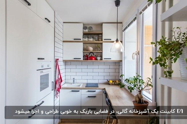 آشپزخانه کم جا با کاشی بین کابینتی سفید، کابینت سفید با صفحه رویی چوبی و یک پنجره بزرگ