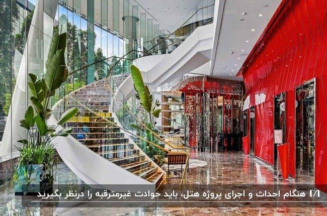 بخش آسانسورهای هتلی با دیوار قرمز براق و راه پله مارپیچ به همراه گلدان های گل طبیعی