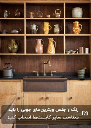 آشپزخانه ای با کابینت های قهوه ای چوبی و ویترین های قفسه ای چوبی