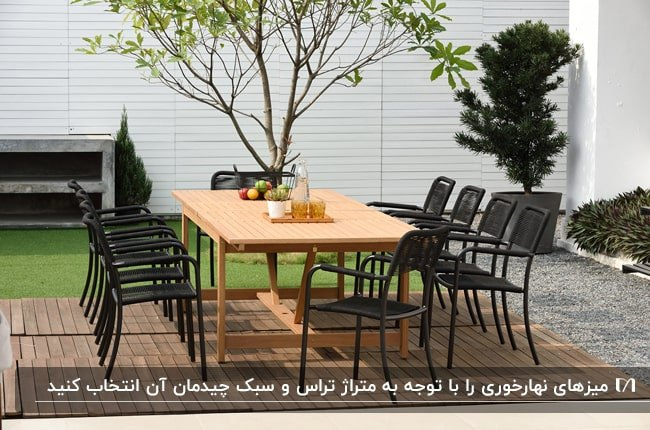 میز مستطیلی چوبی با صندلی های مشکی رنگ غذاخوری در تراس سبز خانه