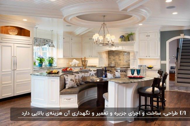 آشپزخانه ای با کابینت های سفید و جزیره منحنی به عنوان میز غذاخوری با نیمکت منحنی و تعدادی کوسن