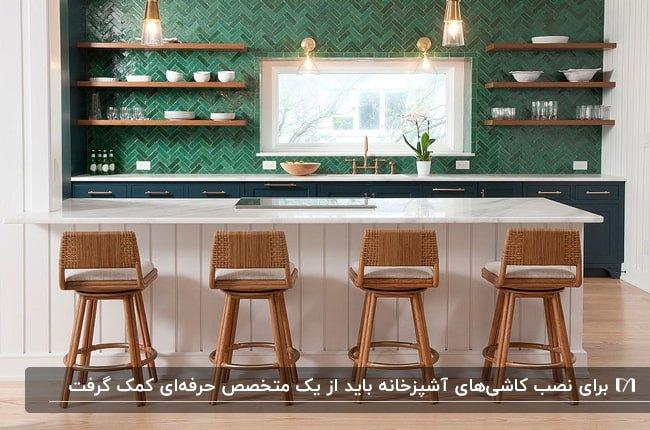 آشپزخانه با کابینت های خاکستری و جزیره سفید، قفسه های دیواری چوبی و کاشی های سبز رنگ