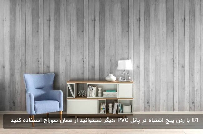 تصویر اتاقی با مبل آبی، قفسه های دکوری چوبی و دیوارپوش پی وی سی خاکستری