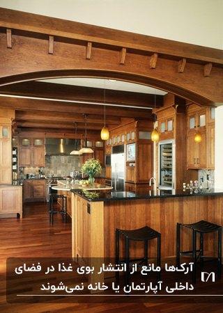آشپزخانه ای با کابینت، کفپوش و آرک چوبی قهوه ای و دو چهار پایه کانتر مشکی
