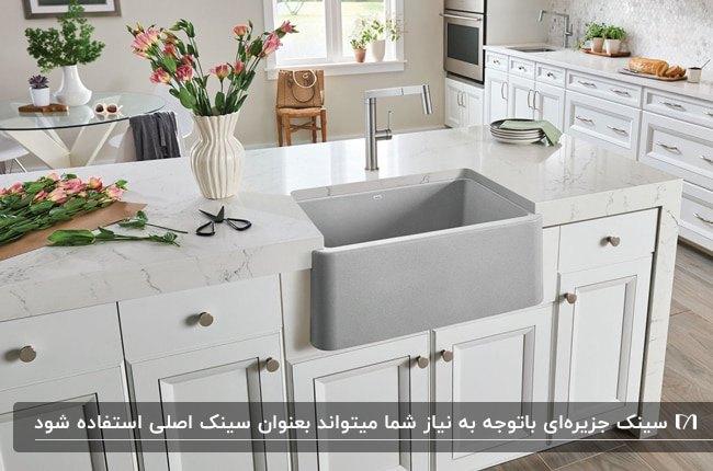 آشپزخانه ای با کابینت ها و جزیره سفید به همراه سینک تک لگنه طوسی در جزیره