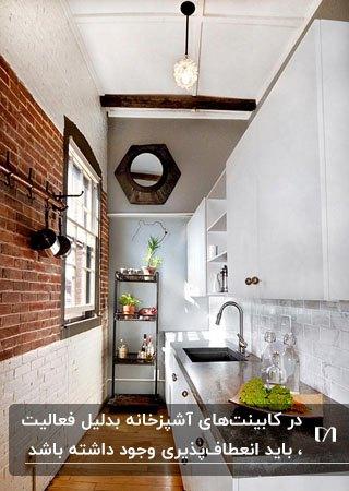 آشپزخانه کوچک و باریکی با دیوار آجری و تقسیم بندی درست کابینت ها
