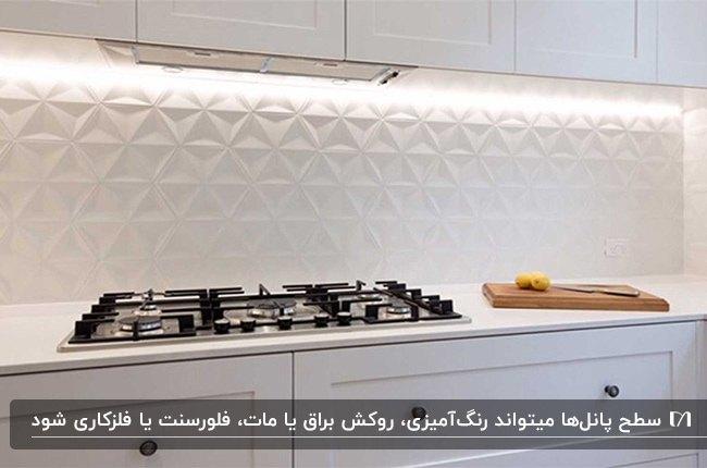 آشپزخانه ای با کابینت ها و پنل های بین کابینتی سه بعدی سفید و اجاق گاز مشکی