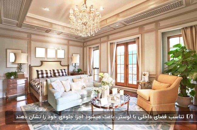 اتاق خواب بزرگی با کفپوش چوبی قهوه ای، مبلمان آبی و نارنجی ، فرش طرحدار آبی و لوستر آویز کریستالی