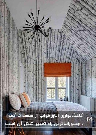 اتاق خوابی با سقف شیب دار، تخت دو نفره و کاغذدیواری کف تا سقف طرحدار سفید و طوسی